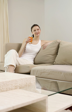 fruit juice: Woman with a glass of fruit juice sitting on the couch