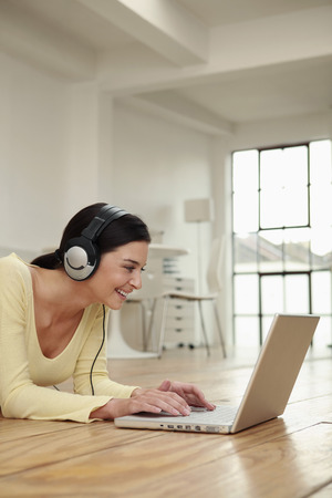 lays forward: Woman with headphones lying forward on the floor using laptop
