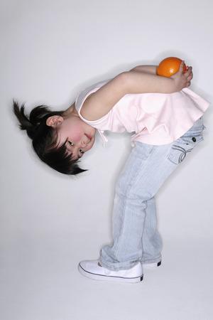 bending down: Ni�a de la celebraci�n de naranja detr�s de su espalda mientras se dobla hacia abajo Foto de archivo