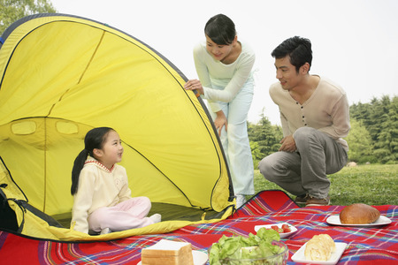 Girl sitting in the tent, man and woman looking at her photo