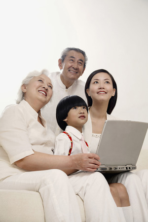 Boy and woman together with senior couple smiling while looking up photo