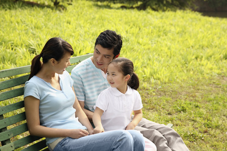 Girl chatting with parents while sitting on the bench
