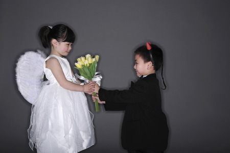 Boy with tuxedo and devil horns giving flowers to girl wearing white dress and angel wings photo