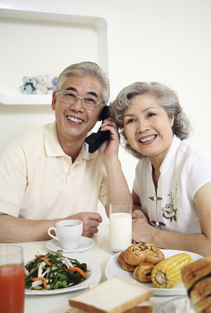 Senior man talking on the phone, senior woman trying to listen photo