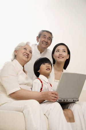 Boy and woman together with senior couple smiling while looking up