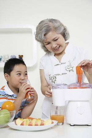 Senior woman putting carrots into juicer, boy drinking carrot juice photo