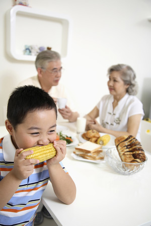 Boy eating corn on the cob, senior man and senior woman having breakfast in the background photo