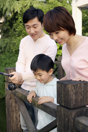 Man fishing, woman and boy watching photo