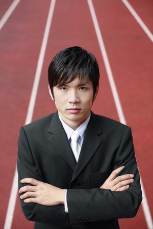 running track: Businessman standing on running track