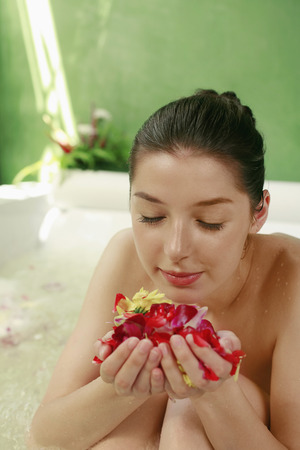 soaks: Woman in bathtub playing with flower petals