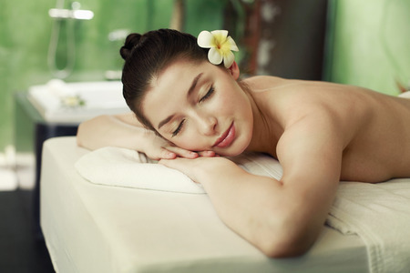Woman lying forward on the massage table with her eyes closed