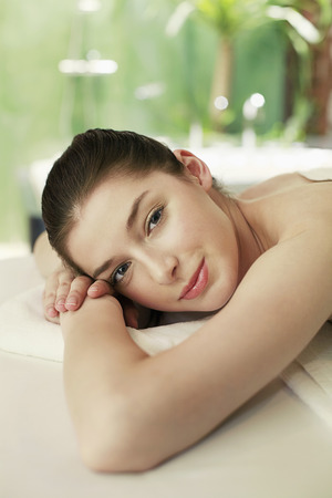 lays forward: Woman lying forward on the massage table Stock Photo