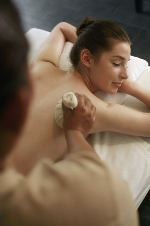 lays forward: Woman enjoying a back massage Stock Photo