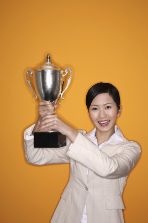 Businesswoman lifting trophy photo