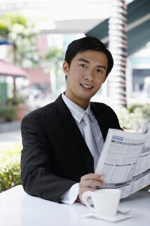 Businessman smiling at the camera while reading newspaper photo