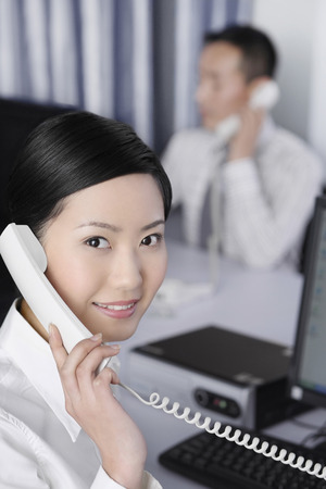 Businesswoman talking on the phone with businessman in the background photo
