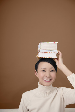 Woman placing a stack of books on her head photo
