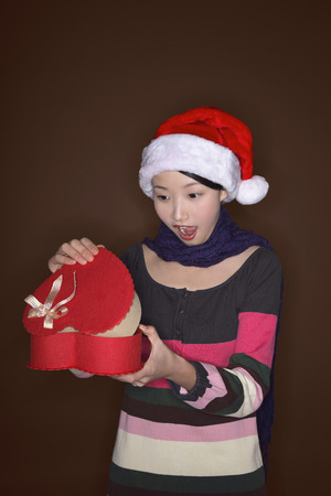 mouth opened: Woman opening present with her mouth opened