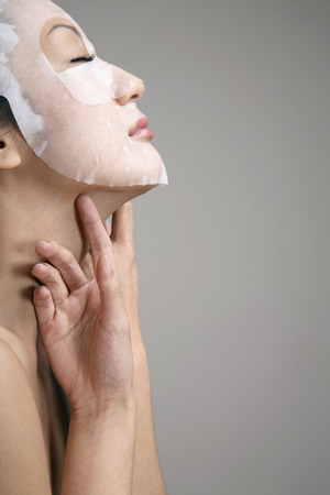 eyes closing: Woman with paper facial mask on her face Stock Photo