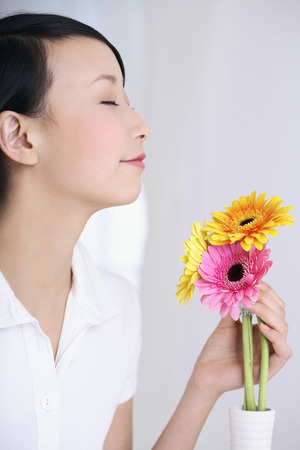 closing eyes: Woman smelling flowers, closing eyes Stock Photo