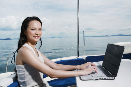 Woman using laptop on yacht photo