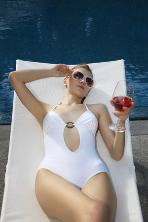 Woman in swimsuit relaxing on lounge chair with a glass of wine photo