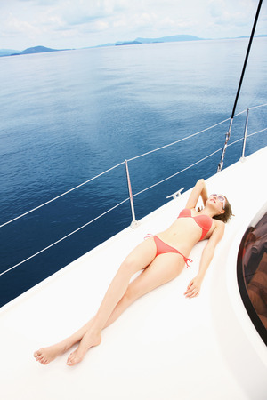 Woman sunbathing on yacht Stock Photo