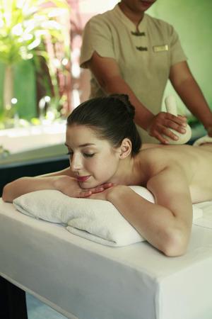 laying forward: Woman enjoying a back massage Stock Photo
