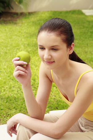 lays forward: Woman with a green apple