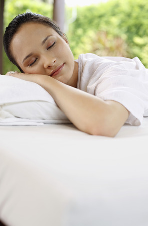 lays forward: Woman lying forward with her eyes closed Stock Photo