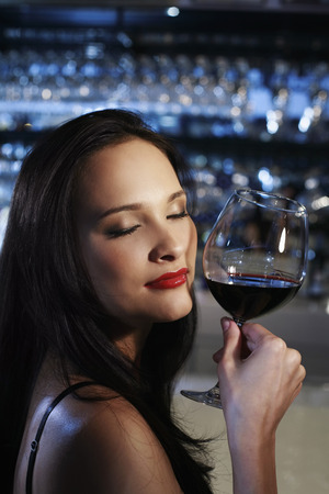 eyes closing: Woman with a glass of red wine closing her eyes Stock Photo