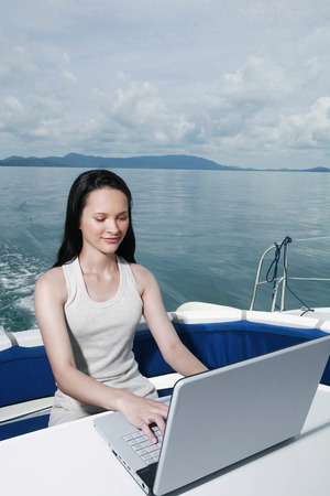 Woman using laptop on yacht Stock Photo