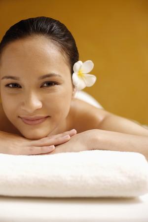 Smiling woman lying forward on the mattress Stock Photo