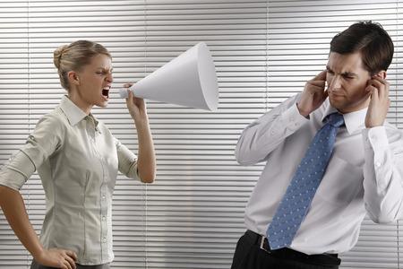 Businesswoman screaming through megaphone, businessman covering his ears