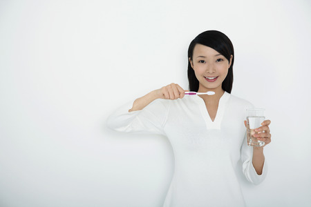 Woman holding toothbrush and a glass of water photo