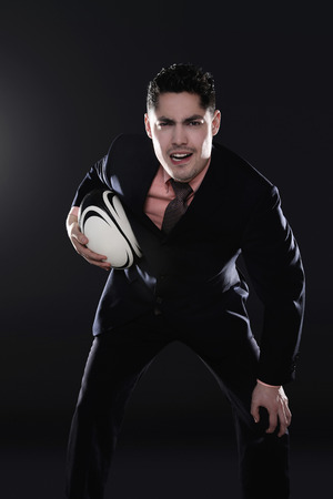 Businessman playing rugby photo