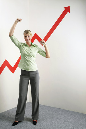 Businesswoman shaking fist in victory, arrow sign going up Stock Photo - 26232983