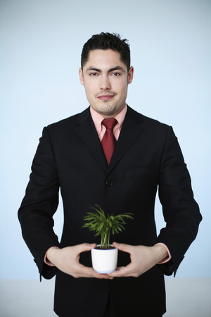 french ethnicity: Businessman holding potted plant