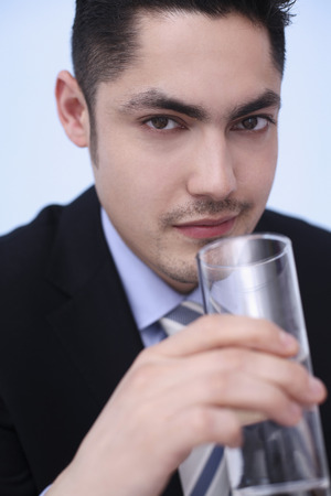 Businessman drinking a glass of water photo