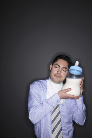 Businessman with baby bibs closing his eyes while holding a giant milk bottle photo