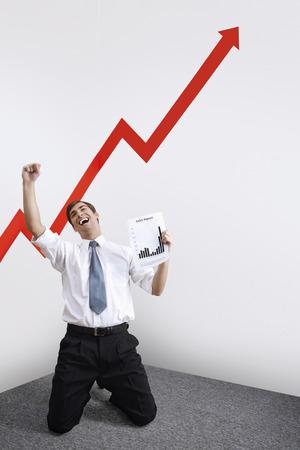 jubilating: Businessman kneeling down celebrating his success, arrow sign going up