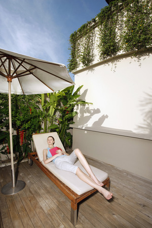 Woman reclining on lounge chair photo