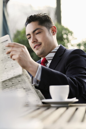 french ethnicity: Businessman smiling while reading newspaper Stock Photo