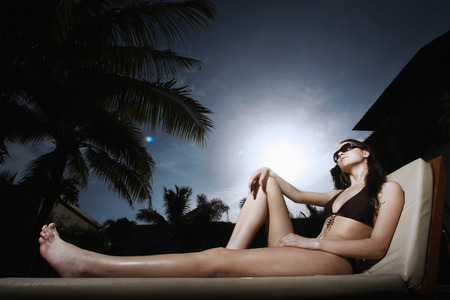 Woman in bikini relaxing on lounge chair photo