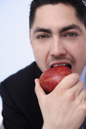 Businessman biting on a red apple photo