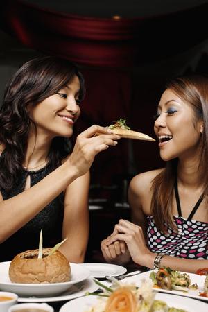 eastern european ethnicity: Woman feeding her friend garlic bread