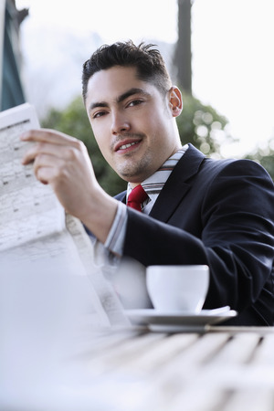 Businessman smiling while reading newspaper photo