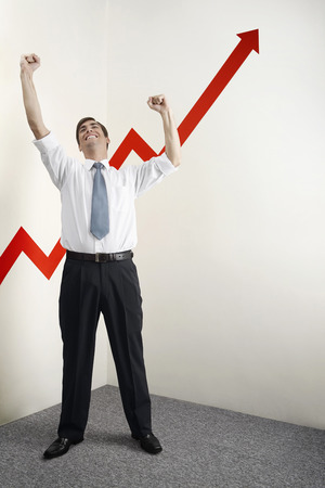 jubilating: Businessman shaking fist in victory, arrow sign going up Stock Photo