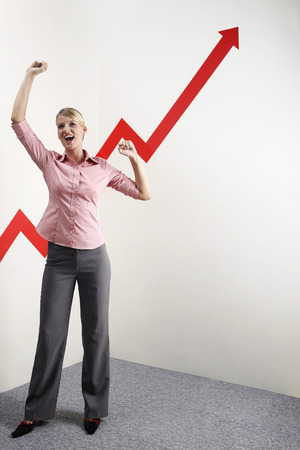 Businesswoman shaking fist in victory, arrow sign going up photo