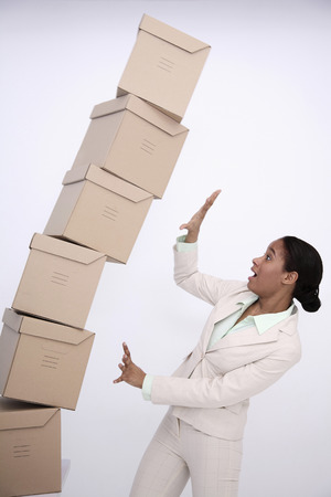 Stacked boxed about to drop on businesswoman photo